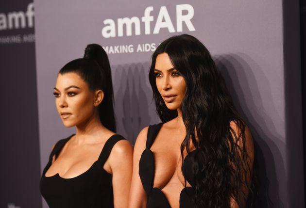 Kourtney Kardashian and Kim Kardashian attend the amfAR New York