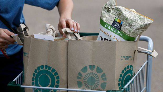 A Whole Foods Market customer prepares to remove her purchases from a shopping basket outside the Jackson, Miss., store, Friday, June 16, 2017. Amazon is buying Whole Foods Market in a deal valued at $13.7 billion, uniting the on-line giant with the grocery store chain that touts fresh organic foods. (AP Photo/Rogelio V. Solis)