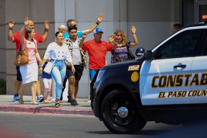 Shoppers exit with their hands up after a mass shooting at a Walmart in El Paso, Texas, on Aug. 3. The store chain has since