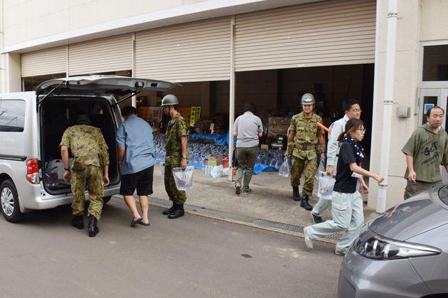 町役場の給水所で6リットル入りの水を受け取り、自家用車に積み込む住民ら=13日、千葉県多古町