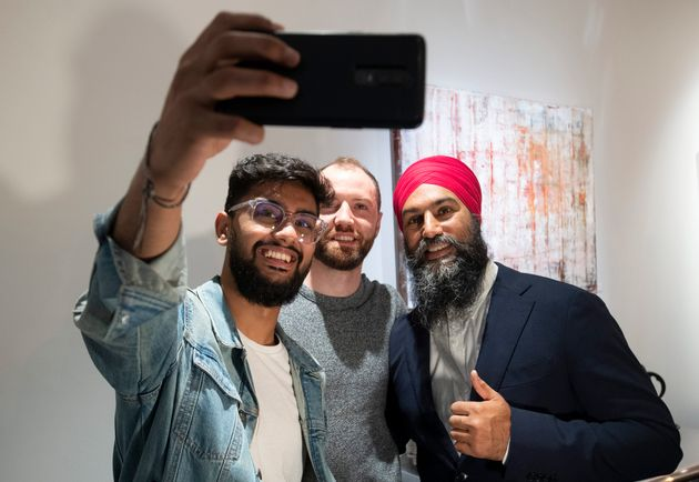 NDP Leader Jagmeet Singh takes a photo with people at a coffee shop following a campaign announcement...
