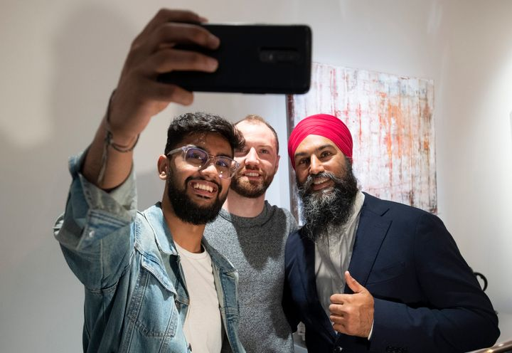 NDP Leader Jagmeet Singh takes a photo with people at a coffee shop following a campaign announcement in Toronto on Friday.