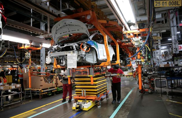 General Motors assembly workers connect a battery pack underneath a partially assembled 2018 Chevrolet...