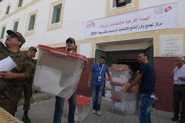 Workers of Tunisia's Independent High Authority for Elections (ISIE) dispatch ballot boxes to polling...