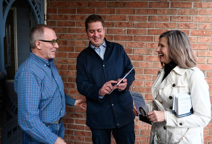 Conservative Leader Andrew Scheer speaks to a resident with Kanata Carleton candidate Justina McCaffrey, right, during a door knocking event in the Kanata suburb of Ottawa on April 25, 2019.