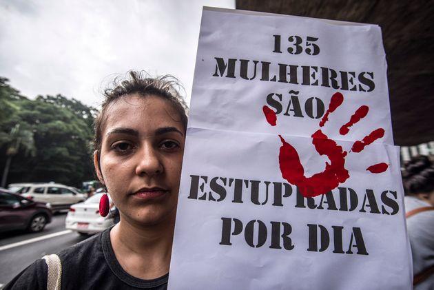 Jovem segura cartaz com dados de 2017 sobre estupro no País. À época, eram 135 por...
