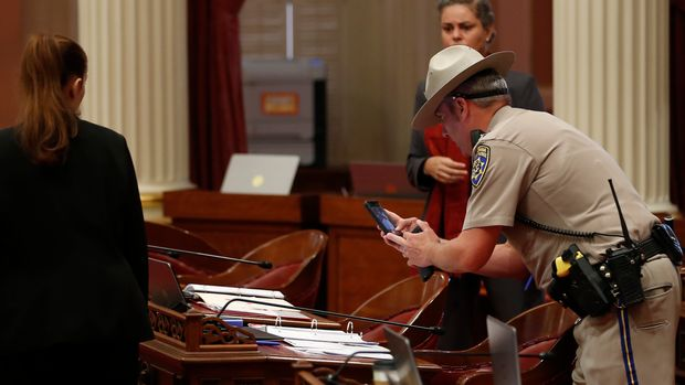 A California Highway Patrol Officer photographs a desk on the Senate floor after a red liquid was thrown from the Senate Gallery during the Senate session at the Capitol in Sacramento, Calif., Friday, Sept. 13, 2019. The Senate was cleared as an investigation is taking place. Authorities took a person into custody.(AP Photo/Rich Pedroncelli)