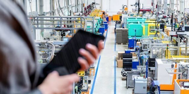 Horizontal color image of businesswoman - unrecognizable person - working with digital tablet in large futuristic factory. Woman standing on top of a balcony, holding touchpad and checking inventory of a manufacturing company on touchscreen tablet. Focus on futuristic machines in background, businesswoman's hands holding black tablet defocused.