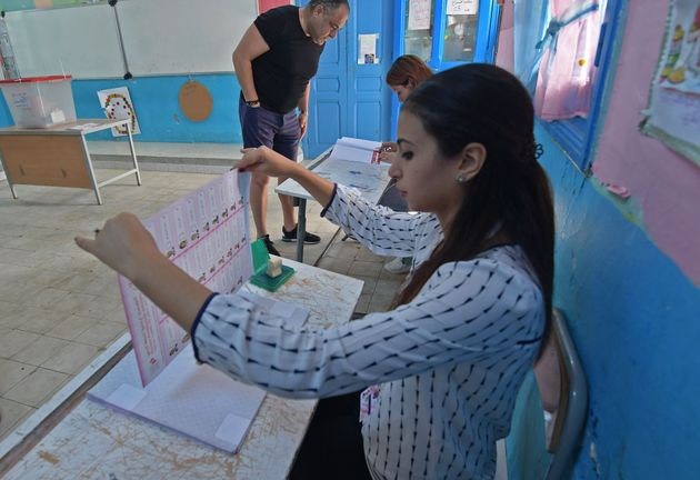 An electoral official holds a list of candidates at a polling station in La Marsa on the outskirts of...
