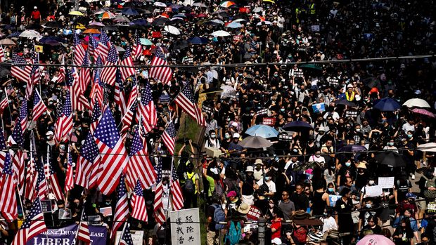 Protesters carrying U.S. flags march on a street in Hong Kong, Sunday, Sept. 15, 2019. Thousands of Hong Kong people chanted slogans and marched Sunday at a downtown shopping district in defiance of a police ban, with shops shuttered amid fears of renewed violence in the months-long protests for democratic reforms in the semi-autonomous Chinese territory. (AP Photo/Vincent Yu)