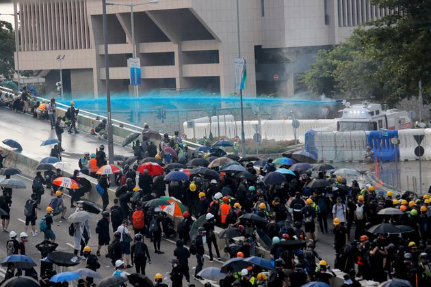 Anti-government protesters are sprayed with a water cannon during a demonstration near Central Government...
