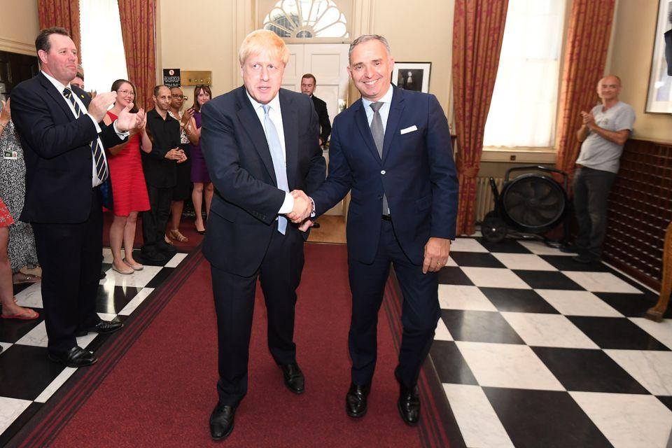 Cummings (extrema direita) enquanto Boris Johnson troca um aperto de mãos com o secretário...