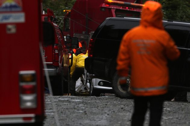 The body of one of the passengers is removed from a passenger bus on a logging road near Bamfield, B.C.,...