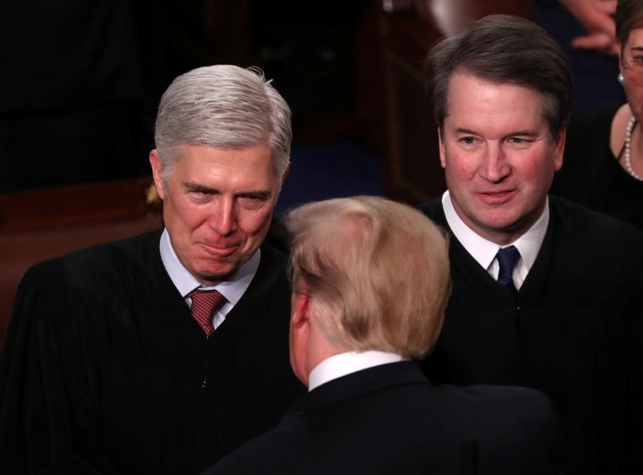 President Donald Trump talks with Supreme Court Justice Neil Gorsuch (L) and Justice Brett Kavanaugh on Capitol Hill in Febru