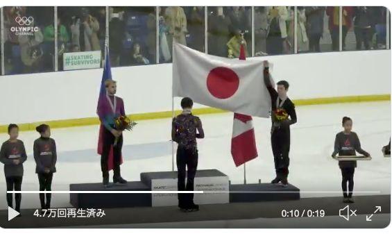 メーシング選手が手で掲揚した国旗に向かう羽生結弦