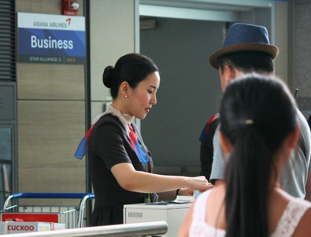 INCHEON, KOREA—AUGUST 2014: An Asiana Airlines flight attendant checks in passengers for boarding at...
