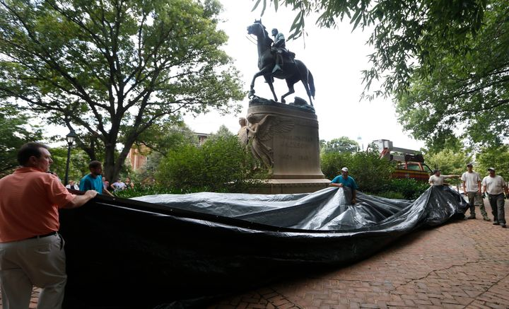 City workers preparing to drape a tarp over the statue of Confederate general Stonewall Jackson in Justice park in Charlottes
