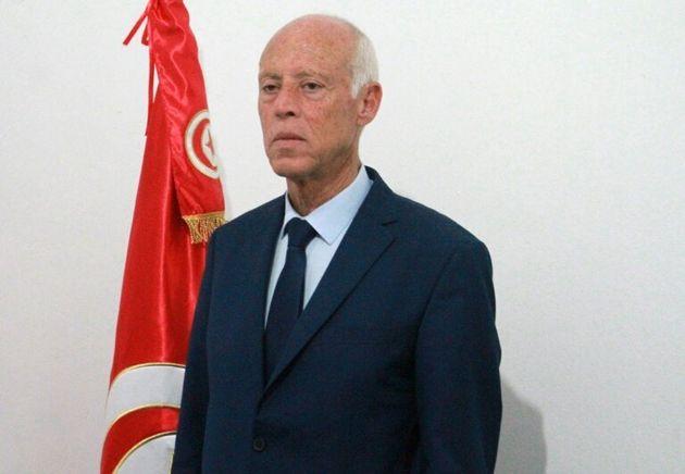 Le candidat indépendant à la présidentielle Kais Saied pose devant le drapeau tunisien, le 15 septembre...