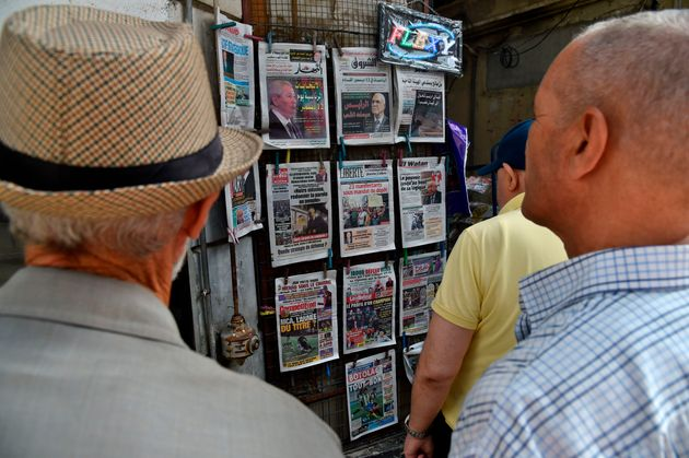 People view the covers of national and foreign newspapers, with the announced Algerian presidential election...