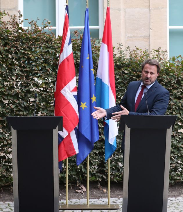 Luxembourg's PM Xavier Bettel gestures towards Boris Johnson's empty podium after his pulled out of a...