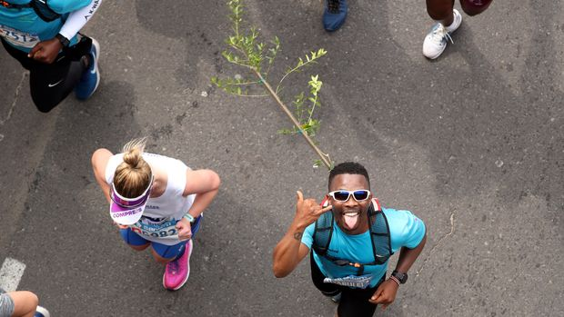 Activist and treegrower Siyabulela Sokomani celebrates as he approaches the final stretch of the Cape Town marathon, in South Africa September 15, 2019. He is one of a group of 20 runners participating in the marathon with saplings on their backs to promote the planting of native trees amid a nationwide push to replace invasive species with indigenous ones to cope with drought and climate change. REUTERS/Mike Hutchings