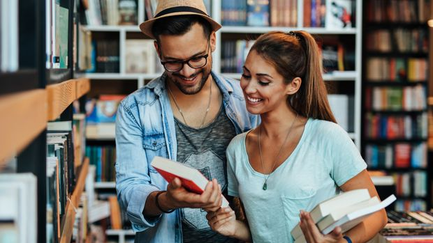 Attractive young students man and woman choosing books in the bookstore