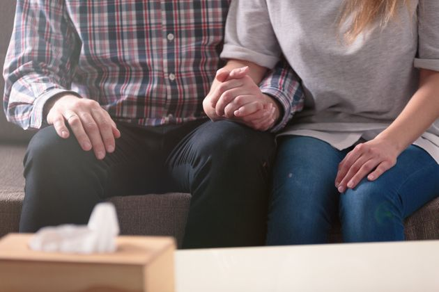 Close-up of a couple holding hands together while sitting on a couch during a