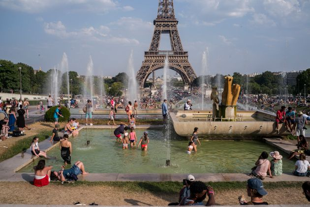 People cool off in the fountains of Paris' Trocadero gardens on July 25, 2019, when a new all-time high...