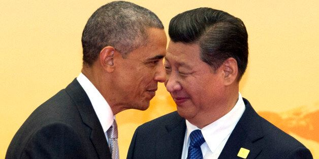 In this Tuesday, Nov. 11, 2014 photo, U.S. President Barack Obama, left, walks past Chinese President...