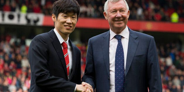Manchester United former player Park Ji-sung, left, shakes hands with former manager Alex Ferguson as...