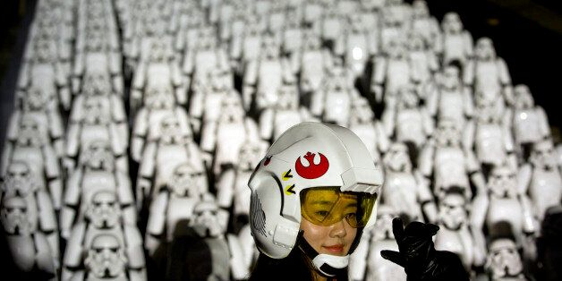 A Chinese Star Wars fan dressed in costume poses for a photo in front of hundreds of miniature storm...