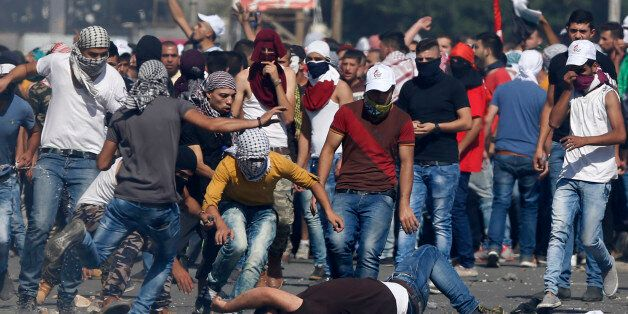 An injured Palestinian demonstrator is helped during clashes at the Hawara checkpoint near of the West...