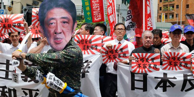 An activist dressed as Japanese Prime Minister Shinzo Abe poses with Japanese military flags