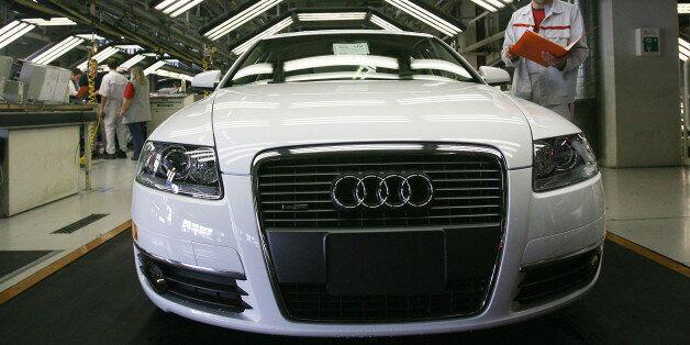 Ein Mitarbeiter der Endkontrolle ueberprueft einen Audi A6 im Lichttunnel in der Produktion bei der Audi...