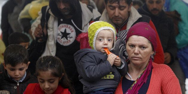 A woman carries a baby and arrives with others at the transit camp for refugees near the southern Macedonian...