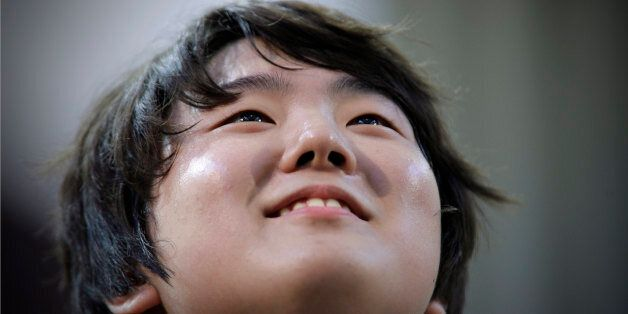 Jin Cho of Korea reacts after playing piano during the third round of XIV International Tchaikovsky Competition...