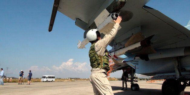 In this photo taken on Monday, Oct. 5, 2015, a Russian pilot fixes an air-to-air missile at his Su-30...