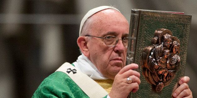 Pope Francis raises the book of the Gospels as he celebrates the opening Mass of the Synod of bishops,...