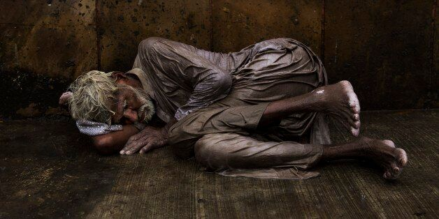An Indian homeless man tries to sleep on a wet street during monsoon rains in New Delhi, India, Saturday,...