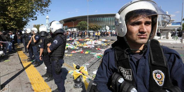 Turkish police officers secure the area at the site of an explosion, where the bodies of victims were...