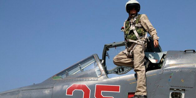 In this photo taken on Saturday, Oct. 3, 2015, Russian army pilot poses at a cockpit of SU-25M jet fighter...
