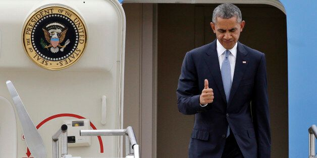 President Barack Obama gives a brief thumbs-up sign as he arrives Friday, Oct. 9, 2015, at King County...