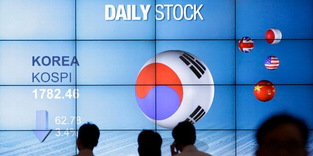 People walk past in front of the screen showing Korea Composite Stock Price Index (Kospi) in Seoul, South...
