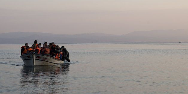 Syrian refugees arrive on a fishing boat from Turkey on the shores of the Greek island of Lesbos , as...