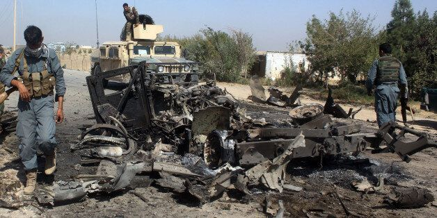 Afghan security forces inspect the site of a U.S. airstrike in Kunduz city, north of Kabul, Afghanistan,...