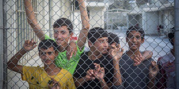 Refugees observe Greece and Austria Prime Ministers from behind a fence at the Moria camp in Lesbos island...