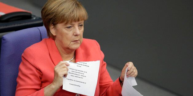 German Chancellor Angela Merkel shreds the script of her speech after she delivered a government statement...