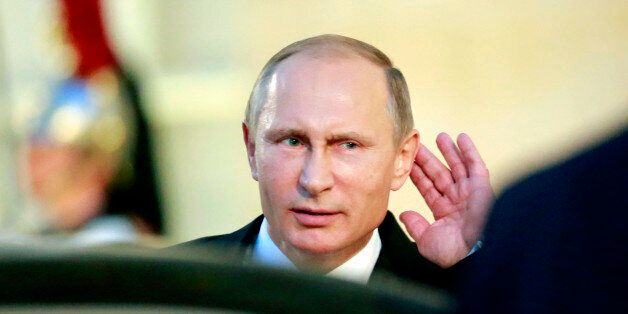 Russian President Vladimir Putin holds his hand on his ear while listening to a newsman's question...