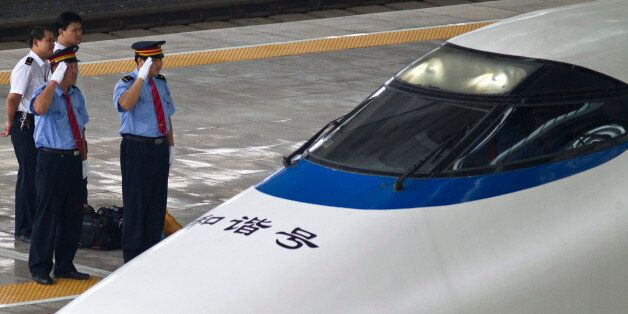 Train drivers salute as a CRH high-peed train arrives at Beijing South Station in Beijing Friday, Aug....