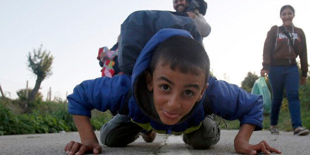 A migrant boy jokes with the photographer whilst heading to cross the border between Serbia and Croatia,...